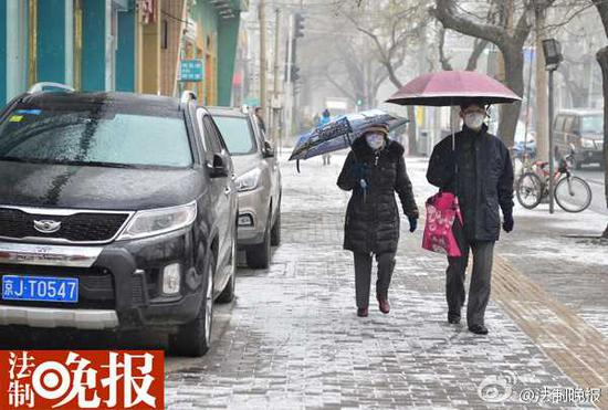 路人打伞挡雪。