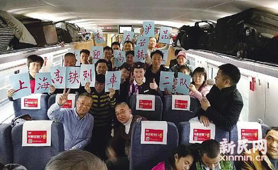图说:列车上的乘客与乘务员一起举起标语庆祝首趟高铁开通 新民晚报记者 方翔 摄