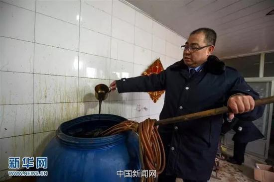 执法人员在展示造假者勾兑的酱油。