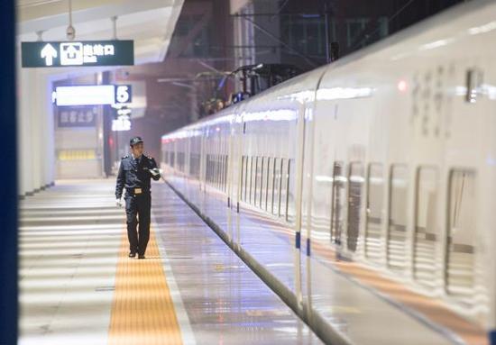 1月12日,在重庆万州北火车站站台上,工作人员对万州始发的首趟春运高铁动车进行检查。