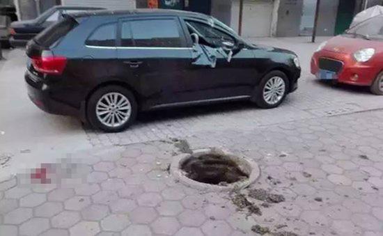 事发地点位于小区内一车库附近,井盖已经被炸得不知去向,一辆黑色轿车停在旁边,因爆炸右半部分严重变形。