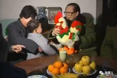 """在农民家里,江泽民、温家宝和主人一起包饺子。拜年过程中,江泽民给老人让座并斟酒,将一个绒毛大公鸡玩具赠给老人的孩子,祝他们""""鸡年大吉""""。"""