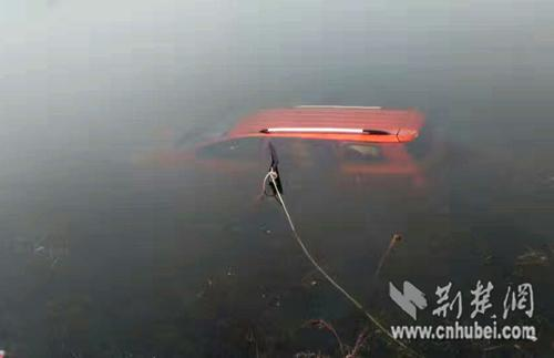 路旁的深水塘中有一辆前后车窗紧闭红色的小车。通讯员 宋俊初 摄