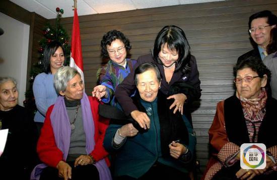 """质料图:2007年11月28日,在加拿大都城渥太华举行的记者召唤会上,加拿大华侨议员邹至蕙(后排右二)给""""慰安妇""""幸存者、我国的刘面换(前排右二)、韩国的张锦朵(前排右一)、菲律宾的费丹齐亚(前排右三)和荷兰的艾伦施舍领巾。(新华网记者杨士龙摄)"""