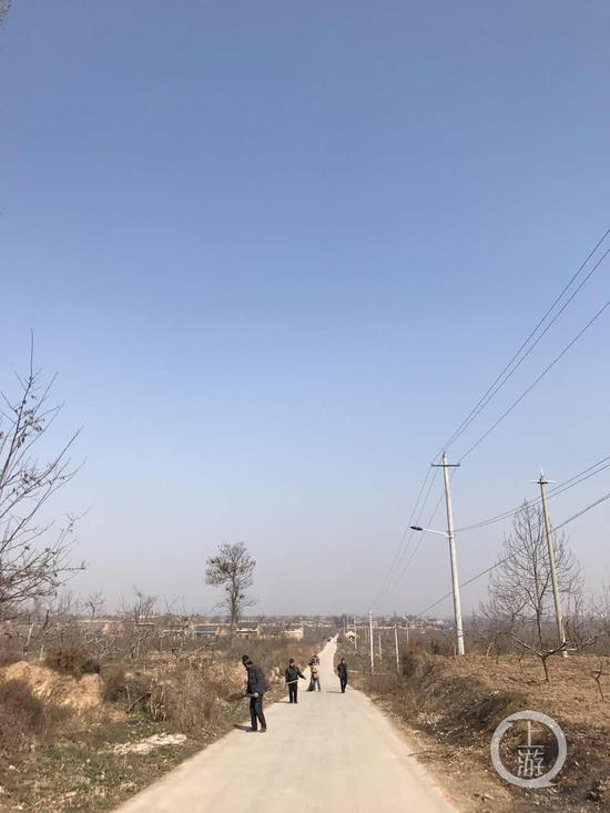 图为村民在打扫公路。