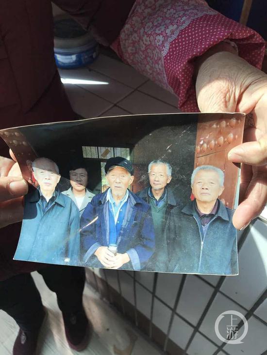 图为王琪弟媳拿着老家兄弟姐妹合影照片。