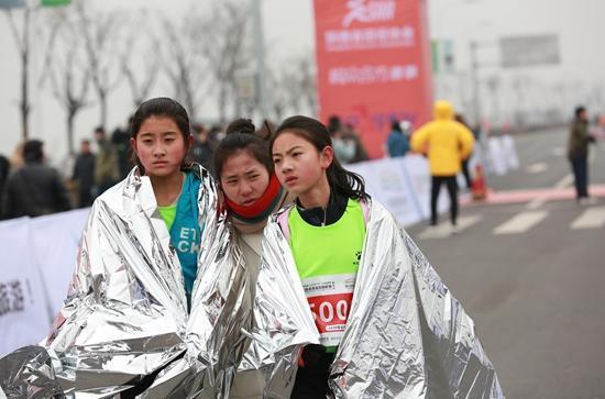 1月15日,3个女孩在西安一场夏季马拉松赛后披着保暖的金属披风。视觉国家供图