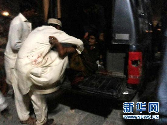 2月16日,在巴基斯坦信德省塞赫万地区,民众在抬运伤者。新华社发。