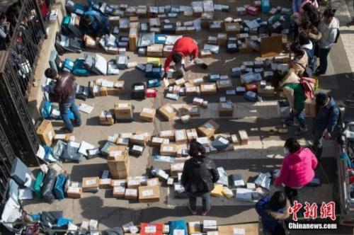 资料图:工作人员忙着分拣满地的快递。 武俊杰 摄