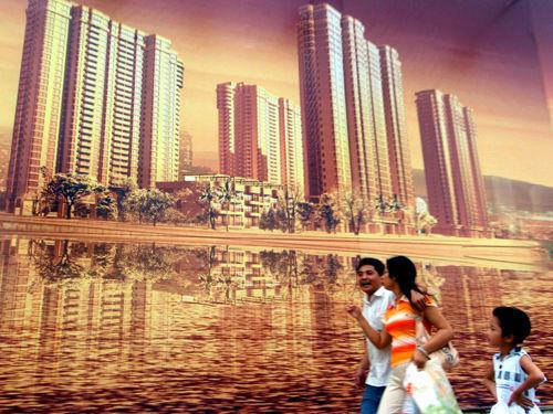 资料图片:市民从厦门市区一大型楼盘广告前走过。新华社记者 张国俊摄
