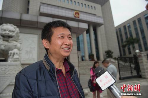 2016年3月30日上午,海南省高级人民法院就陈满申请国家赔偿案举行公开听证。陈满在海南省高级人民法院大门外接受媒体记者采访。骆云飞 摄