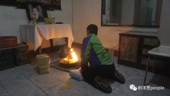 2月19日晚,死者姚永胜12岁的儿子跪在出租屋搭设的灵位前烧纸钱。