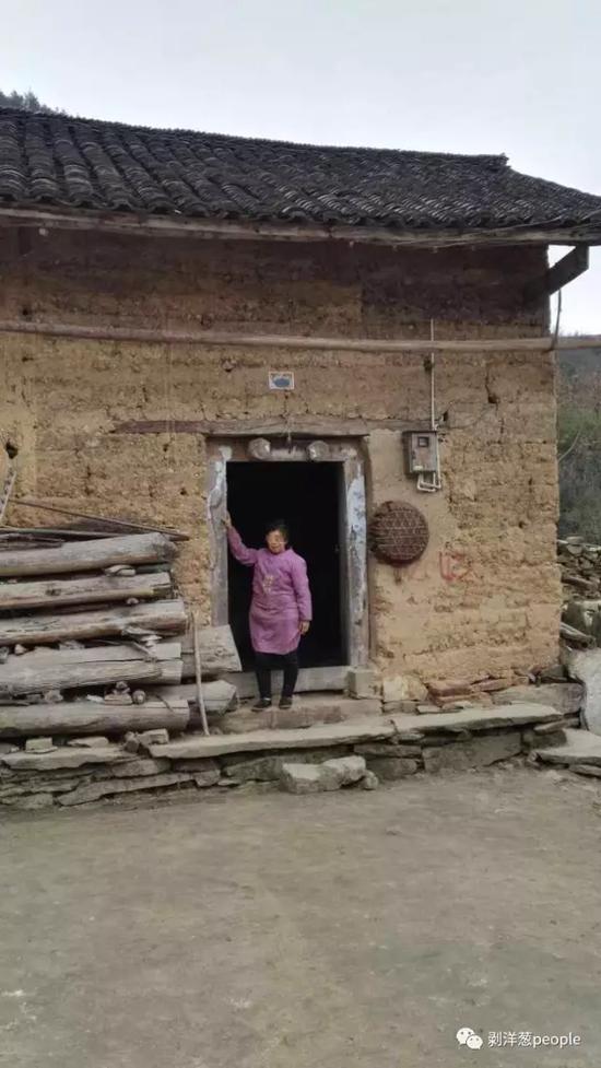 姚永胜老家的房子,他的母亲站在门口,还不知道儿子死亡的消息。村民提供。
