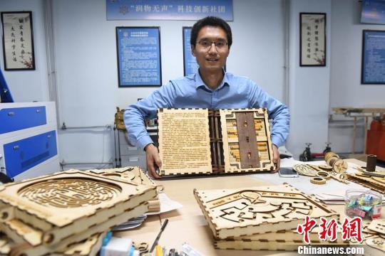 兰州市外国语学校青年生物教师高飞,以故事《海底城的国王》为内容,自学激光切割技术,用木头做出了一本解谜机关书。 杨艳敏 摄
