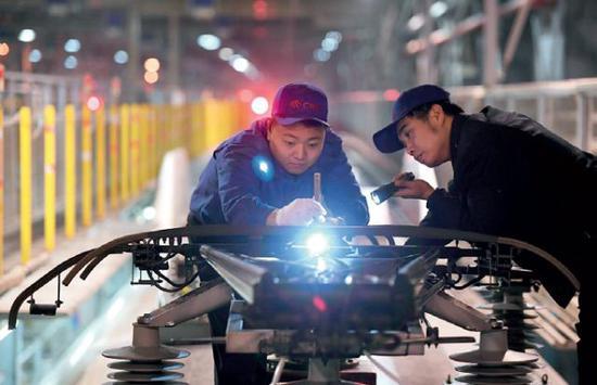 北京动车段西动车所的检修师傅在测量受电弓碳滑板尺寸。(陈晔华摄/本刊)