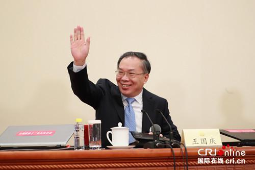 发言人王国庆向现场记者招手。摄影:沈��
