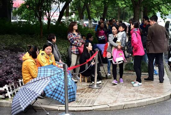 在合肥经开区一所私立幼儿园门口,报名的家长们已排队等候20多个小时(2016年5月10日摄)。 新华社记者刘军喜摄