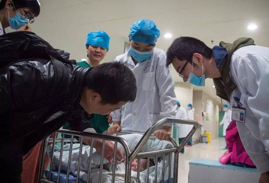 安徽医科大学第一附属医院产房外,助产士将一个刚出生的婴儿送到父亲身边(2016年4月8日摄)。 新华社记者 郭晨 摄