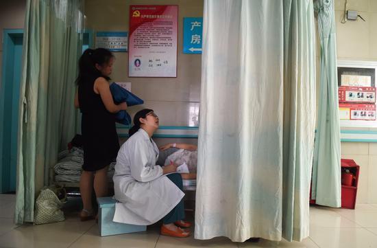 安徽医科大学第一附属医院产科病房内,程桂林医生(左二)向一位加床的产妇询问产前情况(2016年6月29日摄)。新华社记者 郭晨 摄