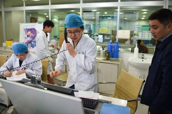 安徽医科大学第一附属医院产科的张晓慧医生(前中)为一位急需入院的产妇联系加床(2016年3月15日摄)。新华社记者 郭晨 摄