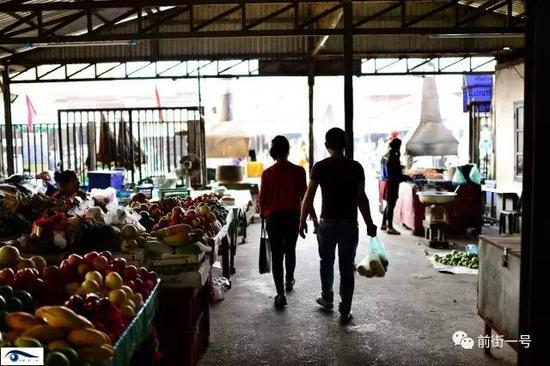 向杰和阿笋在老挝的农贸市场给阿笋父母买水果。