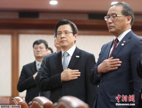 资料图:韩国代总统黄教安(中)在会议上向韩国国旗致敬。在韩国前总统朴槿惠被弹劾后,黄教安曾向国民保证将恢复国政正常运营。他也已表态不参与韩国下届法大选。