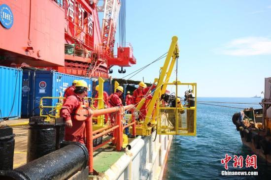 资料图:潜水员乘潜水吊笼下水进行沉船探摸作业。 中新社记者 申海 摄
