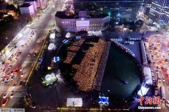 """当地时间2015年4月17日,韩国首尔,4160名手举蜡烛的民众在首尔广场组成""""世越号""""船体的形状,纪念""""世越号""""客轮沉没一周年。"""