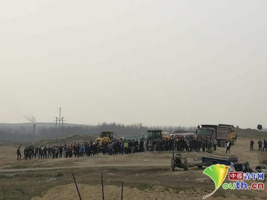 不明身份的社会人员聚集在军里村