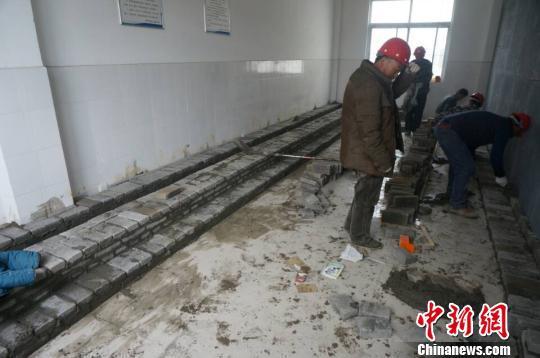 图为23日上午,工人们正在对学校的厕所实施改造。 韩章云 摄