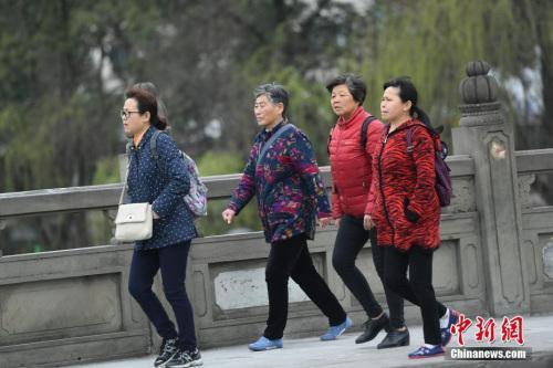 3月14日,四川成都陌头行人身着厚衣物出行。受北方冷空气影响,四川盆地连日来气温连续走低,局部还泛起了降雪天气,民众纷纷添加厚衣物御寒。 中新社记者 张浪 摄