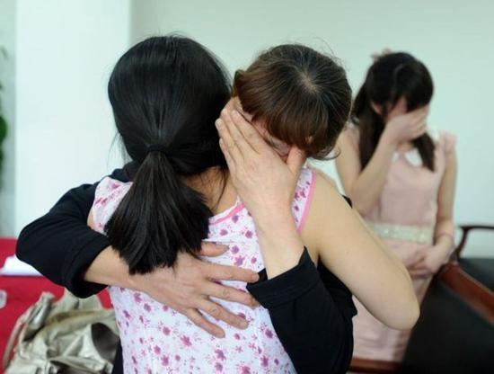 图为詹纳与其中一位母亲拥抱。