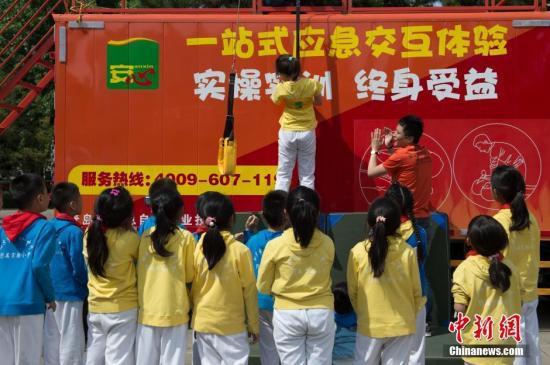 资料图 防灾减灾日北京小学生进行应急体验互动 中新社记者 崔楠 摄