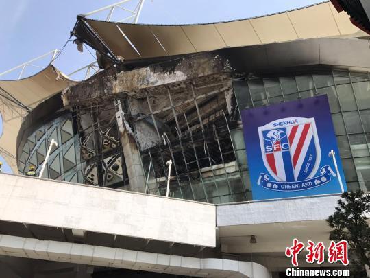 上海虹口足球场顶部的一块顶棚已被烧至脱落,建筑物内部的钢筋结构已清晰可见,上海申花队的宣传旗帜未受火势影响。 王子涛 摄
