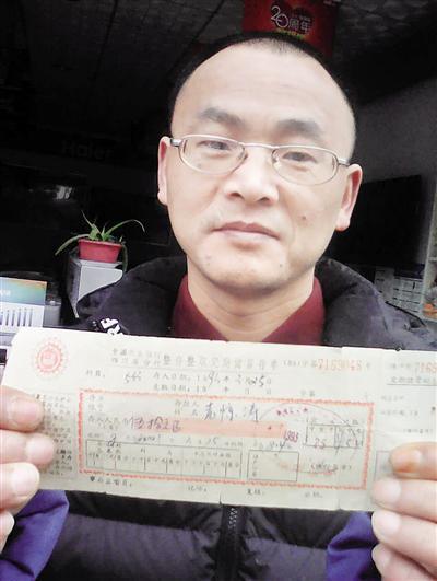 昨日,袁津涛向记者展示24年前的存款单据。 本报记者 胡杰摄