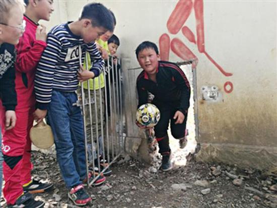 训练比赛时,足球经常被踢到围墙外的田地里,孩子们从墙脚的小洞进出找回足球