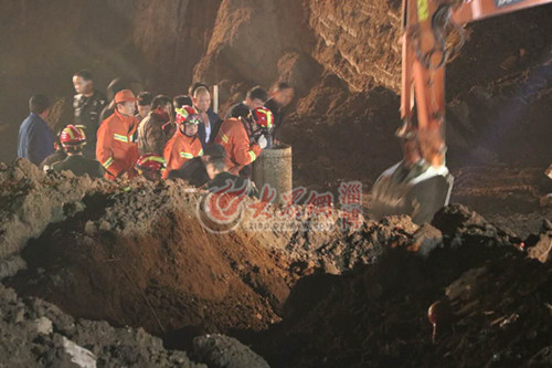 消防队员小心拆除井壁