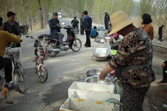 """白洋淀大堤,附近村民在此出售刚刚捕捞上的鱼,""""雄安新区""""成了他们近来的话题"""