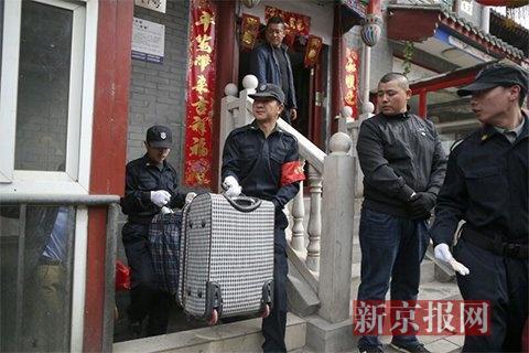 工作人员把住户没来得及取走的物品拿到违建外。新京报记者侯少卿 摄