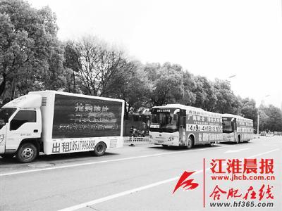 两辆贴满广告的公交车停在池州市区路边。