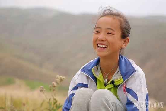 """(""""春蕾女童合唱团""""成员在北京时间的镜头前绽放微笑)"""