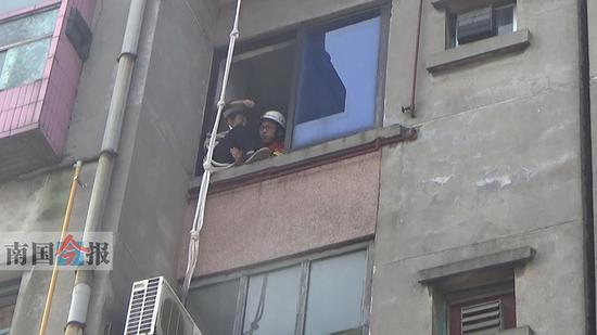 老太被楼顶的消防员拉到自家窗外后,屋内的消防员成功将她救回屋内。通讯员 唐恒 摄