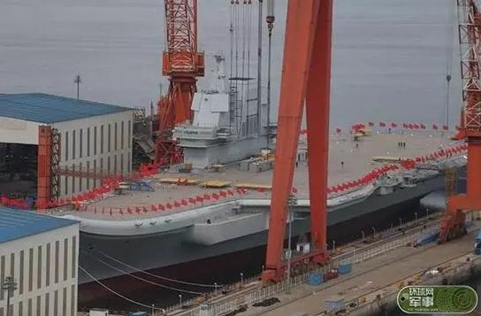 ▲25日下午2时左右,位于大连造船厂船坞里的国产航母有了新动作,工作人员正沿着船体插上一面面红旗。(图片来源:环球时报)