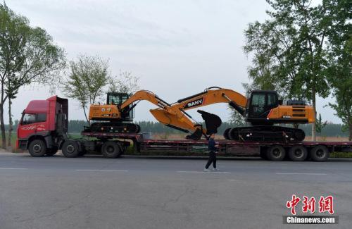 资料图:大型工程车经过雄安新区白洋淀附近的公路。