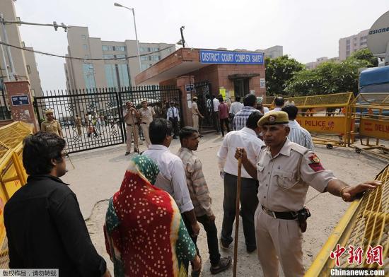 """据外电报道,印度法官当地时间9月13日宣布,判处2012年12月新德里""""黑公交""""轮奸案4名成年被告死刑。图为旁听者排队通过安检进入法院。"""