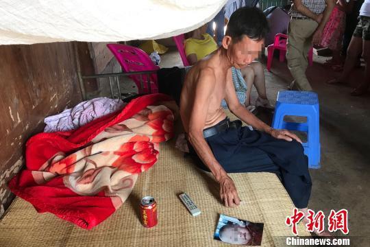 图为林某圣看着孙子孙女的照片。 洪坚鹏 摄