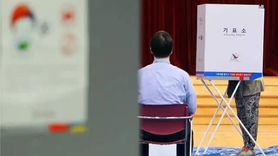 在投票站里,工作人员先向选民介绍投票流程,然后进行身份确认,之后选民在投票纸上确认后投入计票箱。