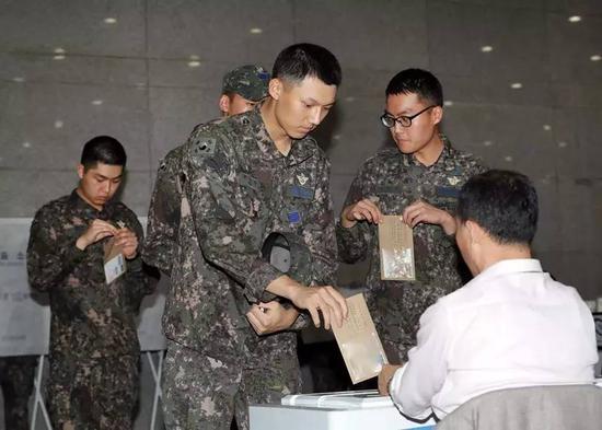"""5月4日,在韩国首尔,几名军人参加总统选举""""事前投票""""。新华社发(李相浩摄)"""