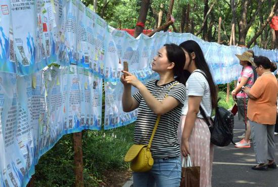 """资料图片:一名市民在济南千佛山公园举行的""""七月七相亲大会""""上用手机记录相亲信息。新华社记者 徐速绘 摄"""