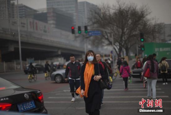 资料图:3月20日,北京市民在雾霾中出行。当日,京津冀环境气象预报预警中心发布的北京地区空气污染气象条件预报显示,北京当天白天大部分地区空气污染气象条件等级为3-4级。 中新社记者 刘关关 摄